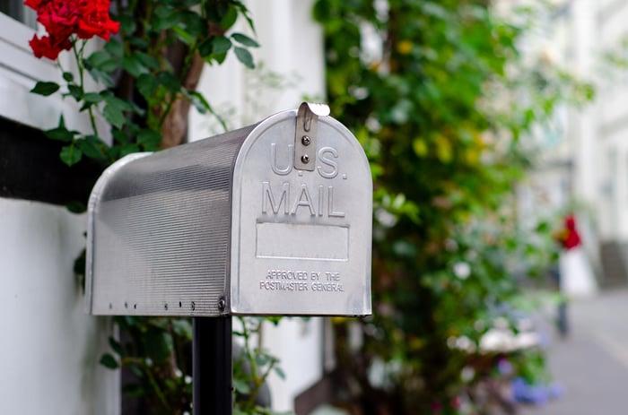 A silver mailbox on a street.