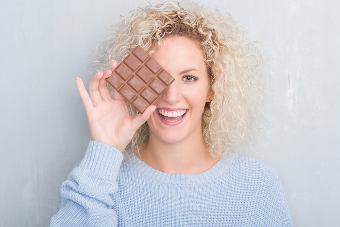 A woman holding a chocolate bar so that it covers one of her eyes