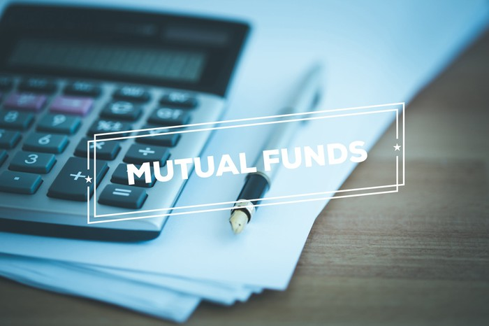 "A calculator sitting on a stack of paper with the word ""mutual funds"" stamped across the top."