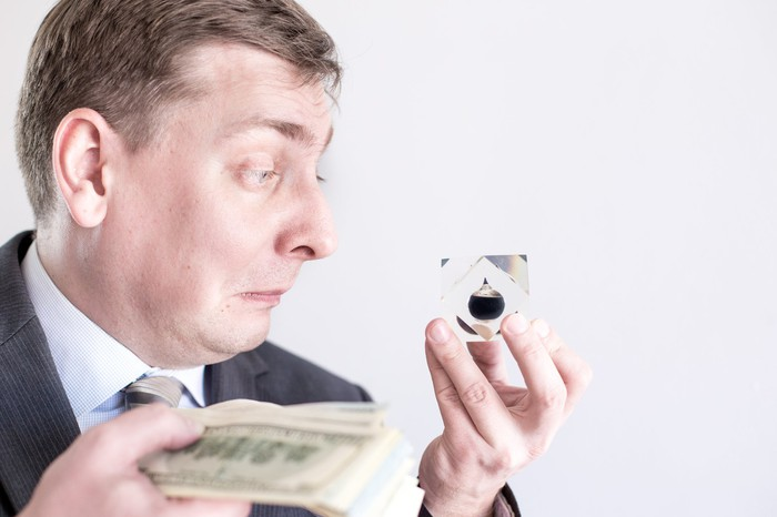 A frowning man holds an oil droplet in one hand and a stack of paper currency in the other.