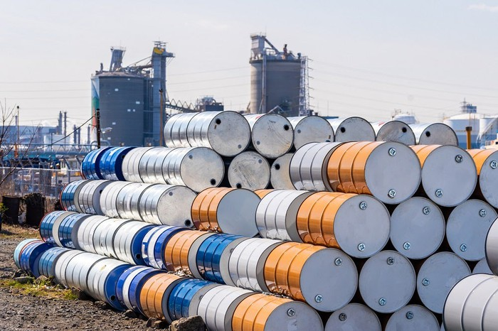 Oil barrels stacked high outside a refinery.