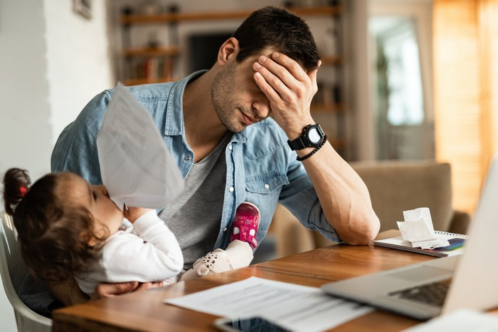 Man at home office with his hand over his forehead while clutching his daughter in his other arm.
