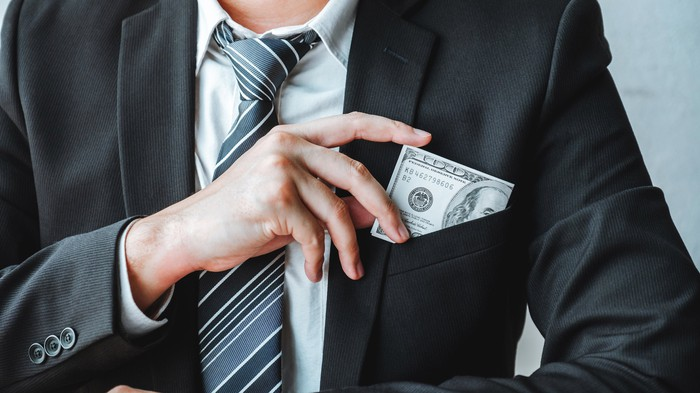 A businessman putting money in his pocket.