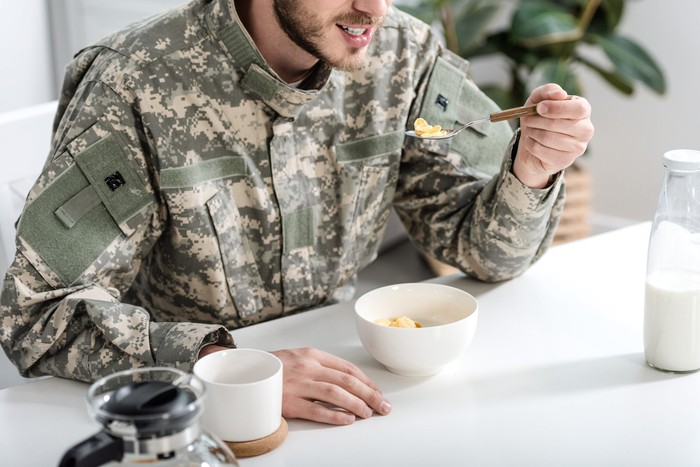 Soldier in camouflage eating breakfast.