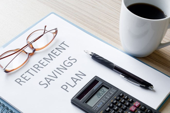 Binder with the words retirement savings plan on wooden surface; eyeglasses, pen, and calculator rest on top of it while cup of coffee sits next to it
