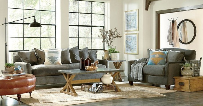 Room with furniture including couch, loveseat, table, ottoman, lamp, mirror, and various accessories along with rug.