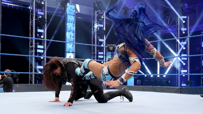 WWE wrestlers performing in the ring.
