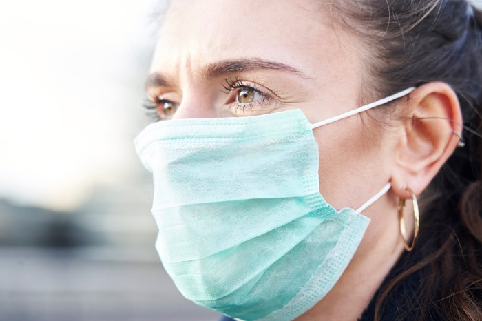 An up-close view of a woman wearing a surgical face mask.