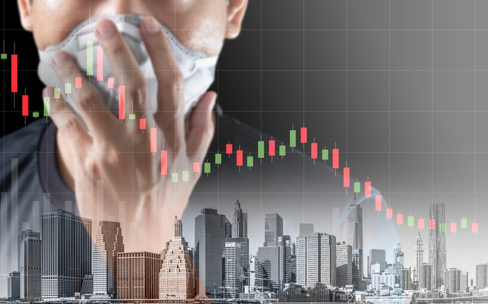 Superimposed over a city skyline and a falling bar chart, a person holds a mask to his face.