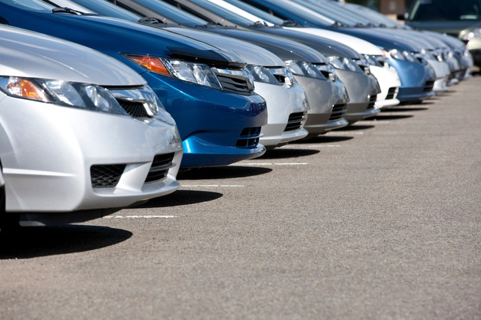 A closeup view of the hoods of several cars parked side by side