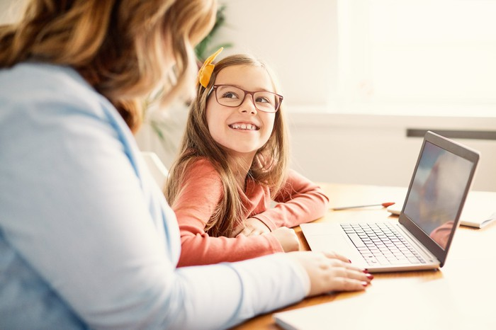 A young child smiling at her mother, with an open laptop on the table in front of them.