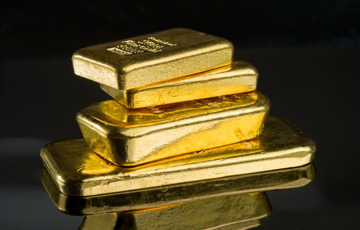 Four gold bars stacked on top of each other.