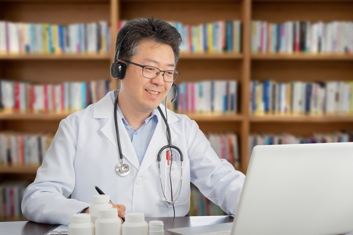 Doctor talking to a patient electronically through a computer.