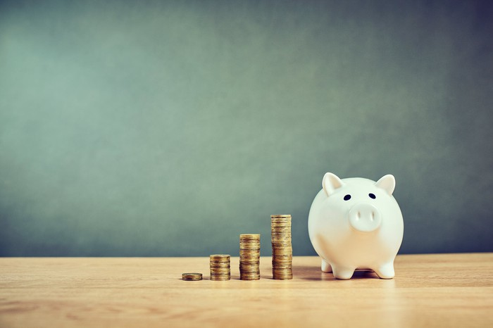 Piggybank and four stacks of growing coins on a table with a chalkboard in the background.