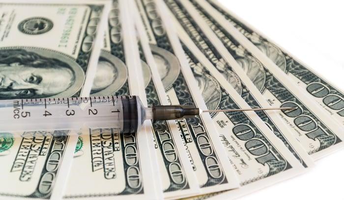 Syringe on top of $100 bills