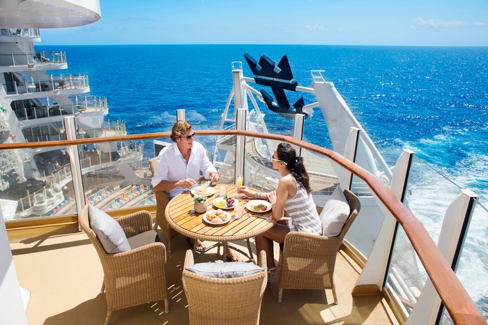 A couple enjoying breakfast on an outdoor deck of a Royal Caribbean ship.