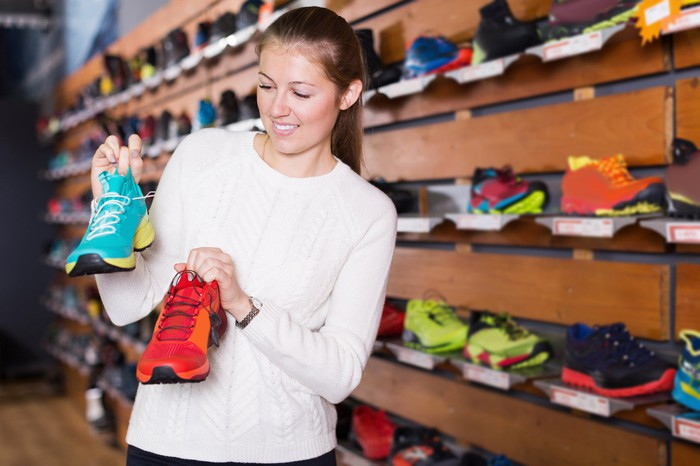 A woman holds up two different sneakers while shoe shopping