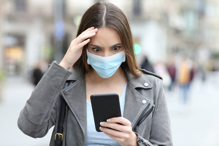 A young woman, wearing a medical face mask, stares wide-eyed at her phone.