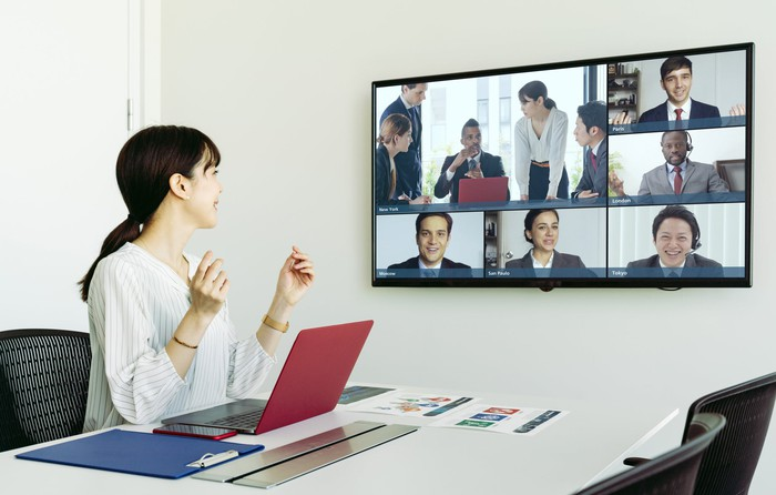 A person at a conference table leads a videoconference.