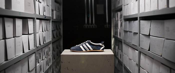 An Adidas shoe on a box in a storage room.