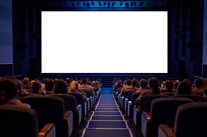 People seated in a movie theater facing a blank screen.