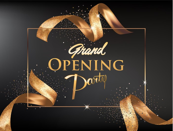 A Grand Opening Party Invitation with gold ribbons and glitter.