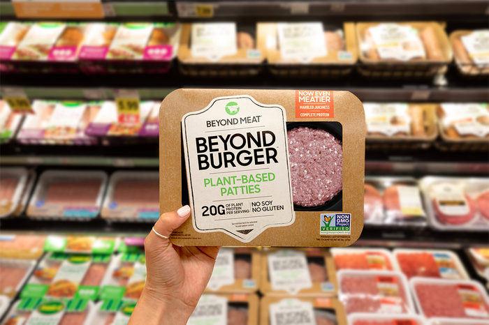 Hand holding up a Beyond Meat patty package in front of a grocery store meat case