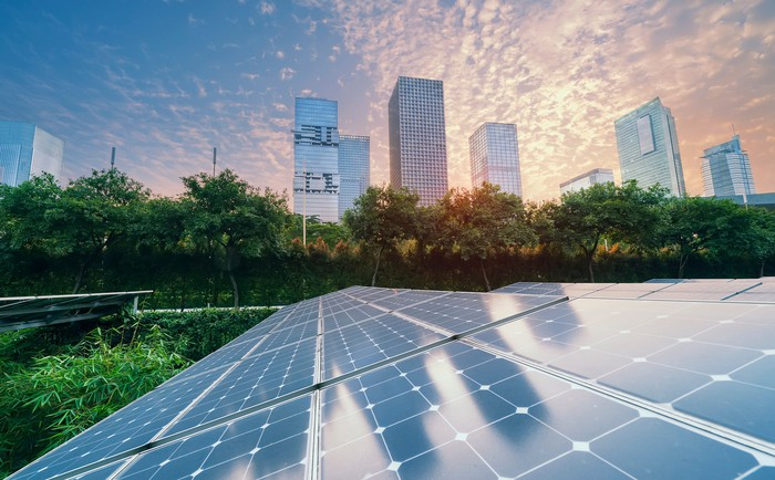 Solar panels with a cityscape in the background.