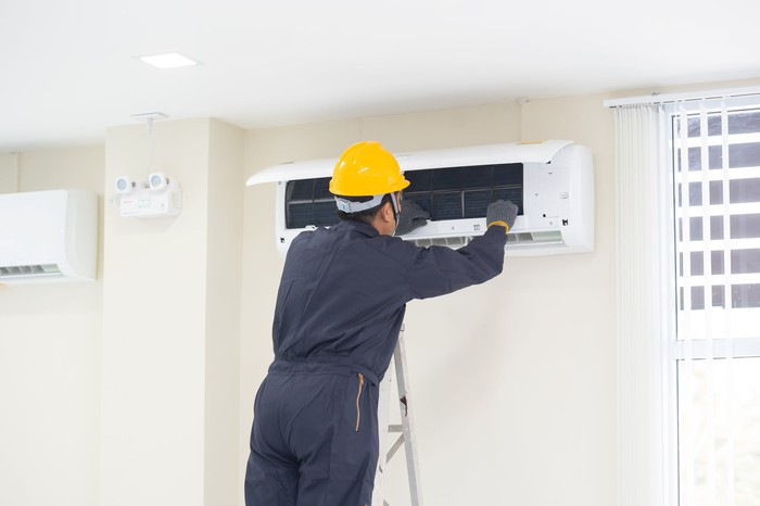 A man repairing a wall-mounted air conditioning unit.