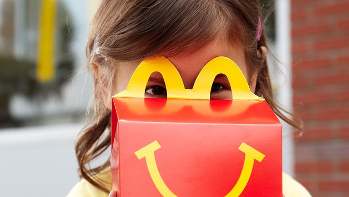 Girl holding up McDonald's Happy Meal box