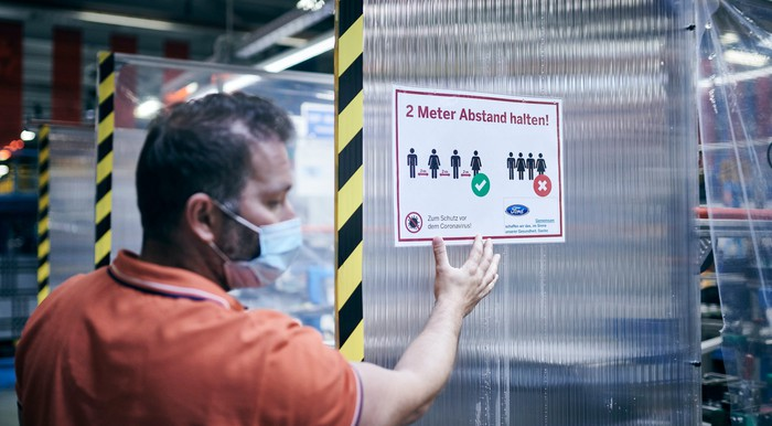 A worker wearing a mask is shown next to a sign reminding employees to maintain social distancing at a Ford factory in Germany.