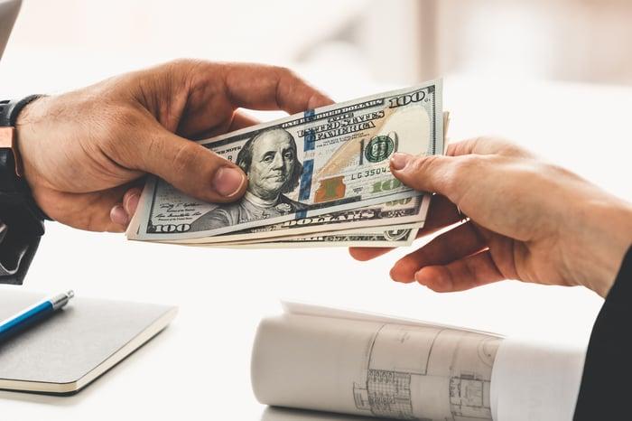 Person handing over money.
