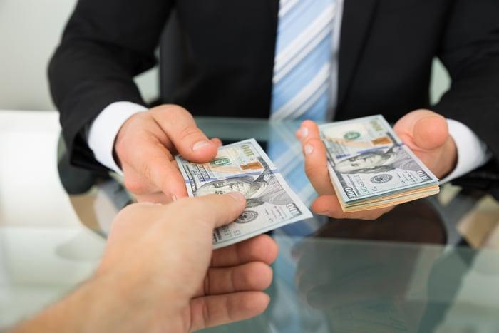 A businessman handing over cash.