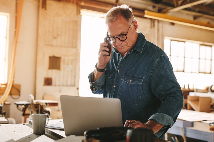 Older man standing at laptop holding phone to ear