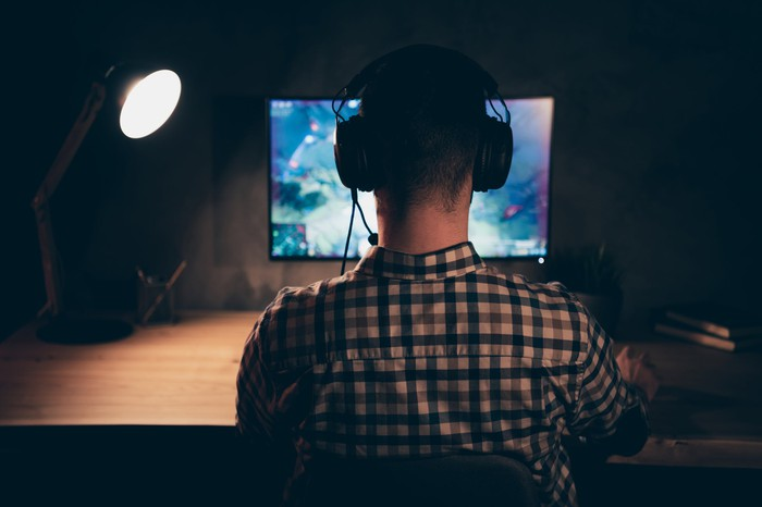 A man wearing a headset, while playing a video game.