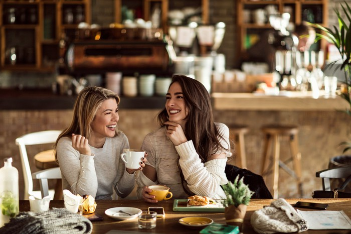 Two women smiling in a coffee shop while holding their mugs.