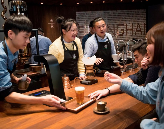 A group of Starbucks workers in China talking around a table.
