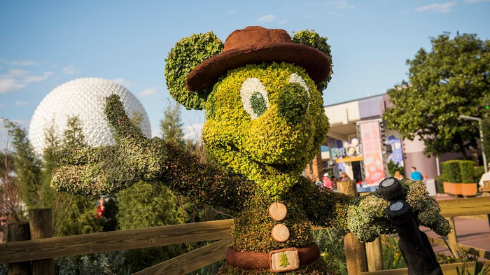 A grass topiary of Mickey Mouse at Disney World's EPCOT. Spaceship Earth is in the background.