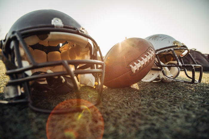 Football helmets and a football placed on a field.