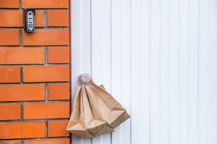 Paper delivery bags hanging on a doorknob.