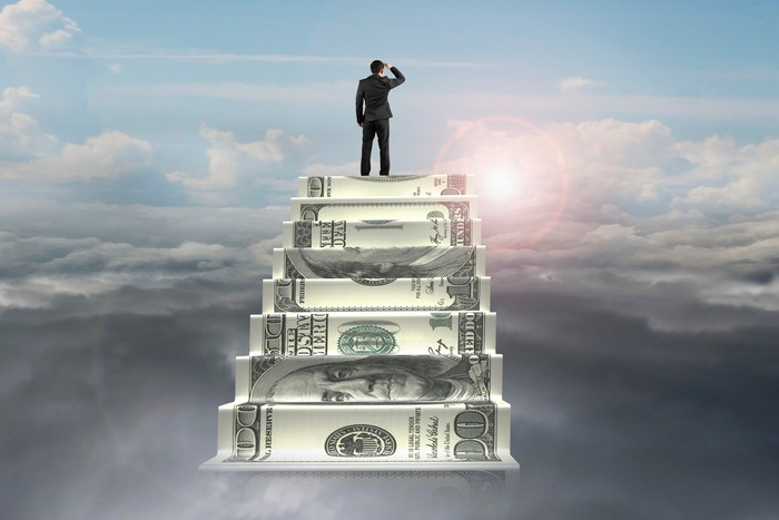businessman on top of money stairs looking at sunlight