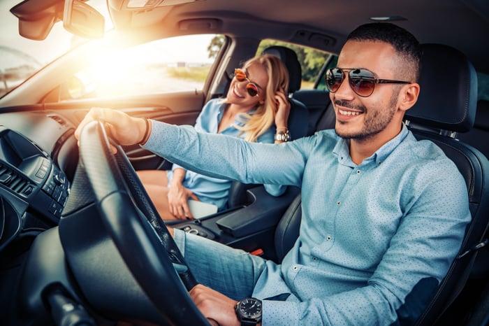 Two people enjoying driving.