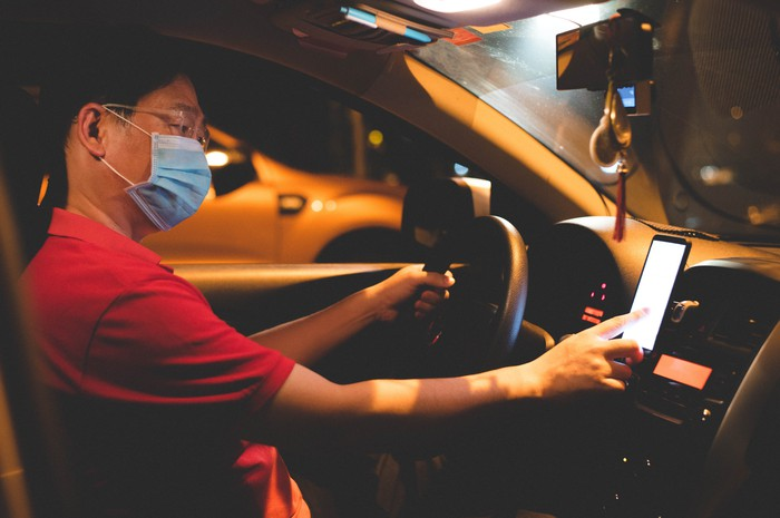 Ride-hailing driver wearing a mask and looking at a GPS map in his car.