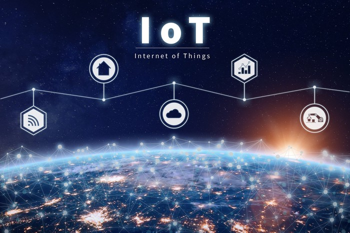 Internet of Things icons suspended above the Earth, with a global connected network lit up
