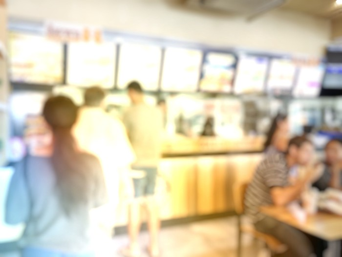 A blurry image of a menu and line of customers at a fast-food restaurant