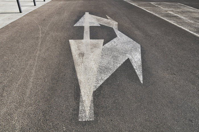 Photo of a street with several traffic-guidance arrows pointing in various directions.