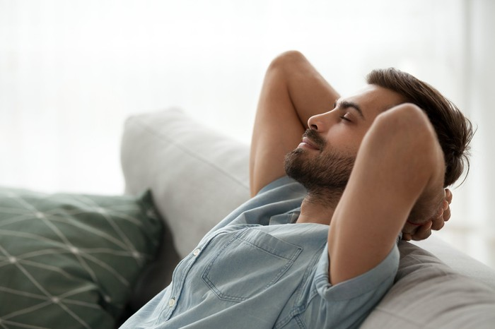 Man with eyes closed leaning back on couch