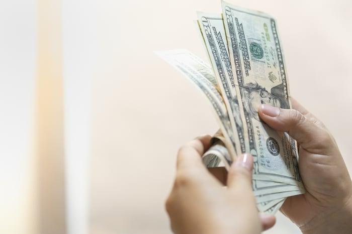 A woman counting a cash bonus.