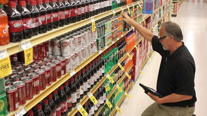 A man checking a grocery store shelf stocked with soft drinks.