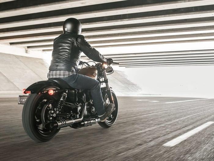 Man riding a motorcycle under an overpass.